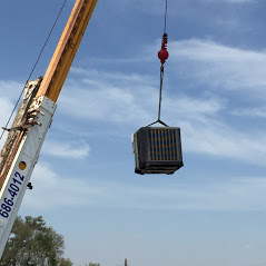 Crane lifting a commercial AC unit in McAllen, TX